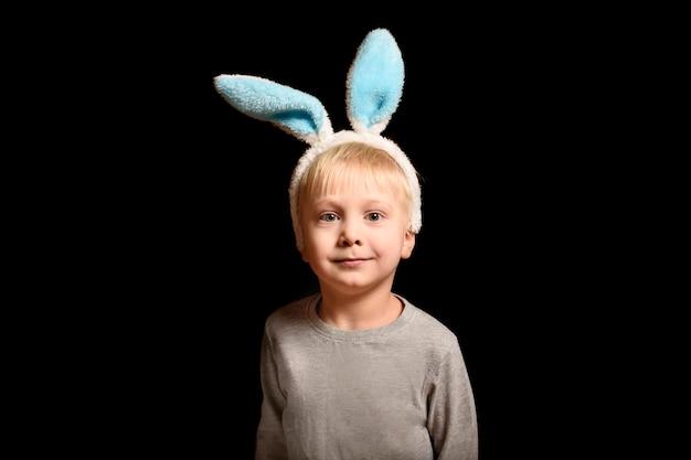 Schattige kleine blonde jongen in de oren van de haas staande op zwart