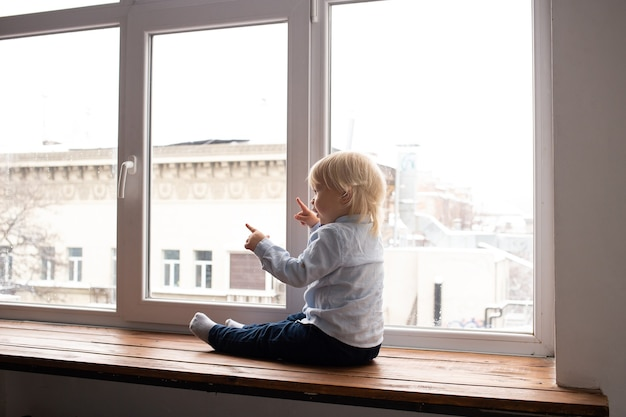 Schattige kleine blonde jongen jongen zittend op de vensterbank. een kind kijkt uit het raam.