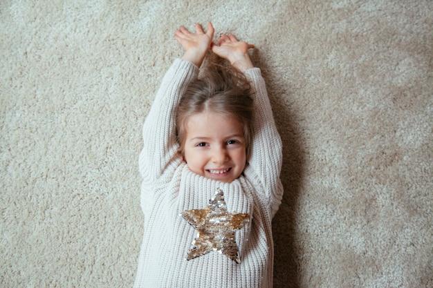 Schattige kleine blonde jongen lachend op de vloer
