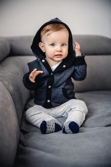 Schattige kleine blonde jongen met blauwe ogen zittend op de bank in de woonkamer met hoodie op het hoofd, met ernstige gezichtsuitdrukking