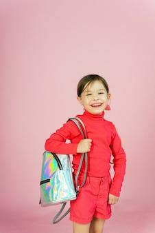 Schattige kleine blonde klasgenoot in een roze pak in de studio met een holografische rugzak. grappige eerste nivelleermachine op een roze pastel achtergrond met copyspace