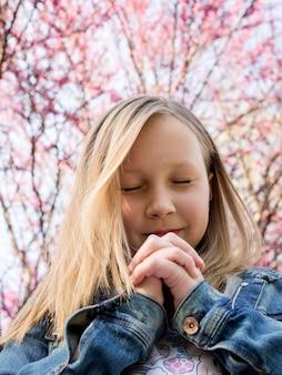 Schattige kleine blonde meisje bidden