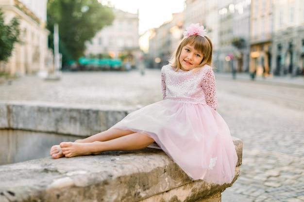 Schattige kleine blonde meisje in een roze jurk in de stad