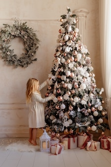 Schattige kleine blonde meisje in jurk in de buurt van de kerstboom