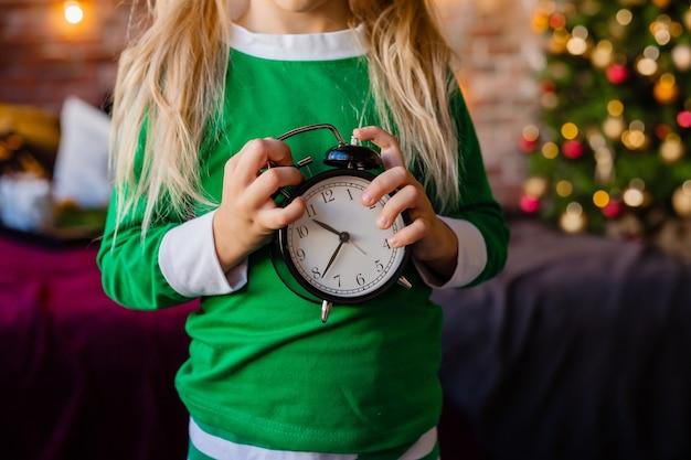 Schattige kleine blonde meisje in pyjama's in de buurt van de kerstboom