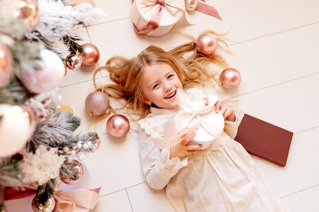 Schattige kleine blonde meisje in retro jurk ligt in de buurt van de kerstboom