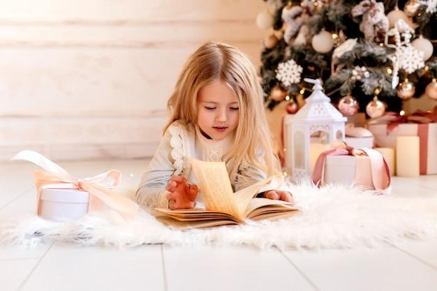 Schattige kleine blonde meisje leest thuis een boek in de buurt van de kerstboom