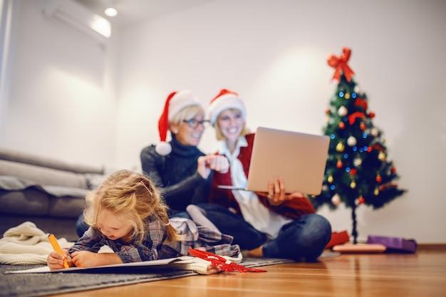 Schattige kleine blonde meisje liggend op de buik op de vloer en tekenen. op de achtergrond zijn oma en moeder met behulp van laptop. kerstmis is tijd voor familie.