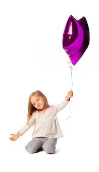 Schattige kleine blonde meisje met paarse ster vormige baloon geïsoleerd op een witte achtergrond