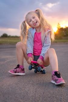 Schattige kleine blonde meisje, zittend op het roze schaatsbord