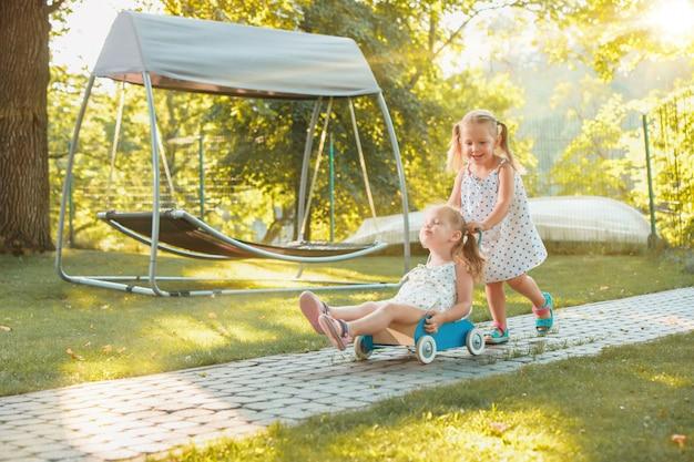 Schattige kleine blonde meisjes rijden op een speelgoedauto in de zomer.