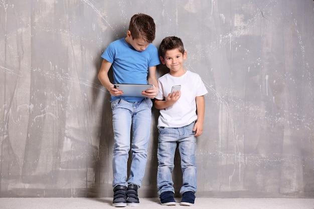 Schattige kleine broers met behulp van gadgets op grijze getextureerde muur