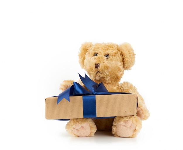 Schattige kleine bruine teddybeer houdt een bruine doos met een blauw lint