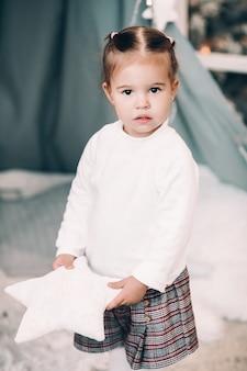 Schattige kleine brunette meisje in witte trui staande in de sneeuw opzoeken