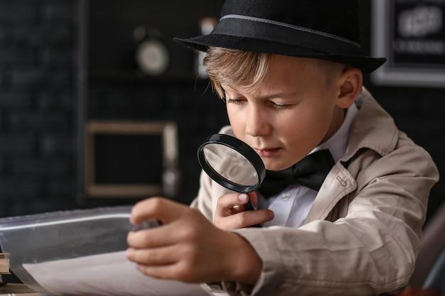 Schattige kleine detective die met bewijs aan tafel werkt
