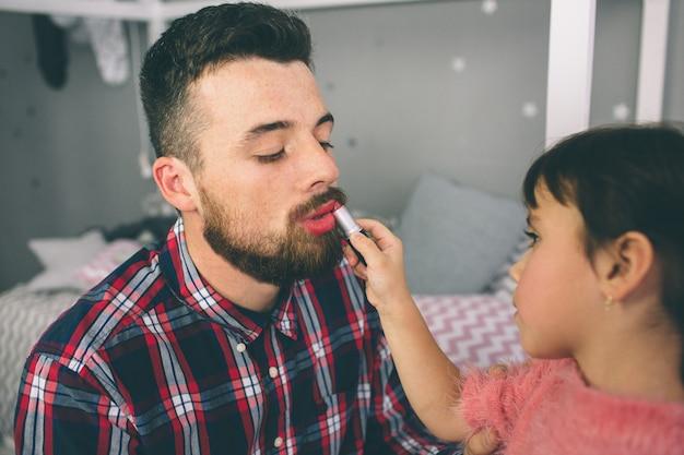 Schattige kleine dochter en haar knappe jonge vader spelen samen in de kinderkamer. meisje doet haar vader een make-up.