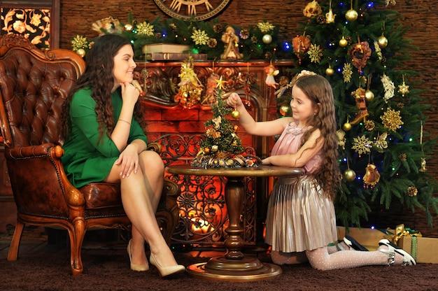 Schattige kleine dochter en moeder poseren in kamer versierd met kerstvakantie