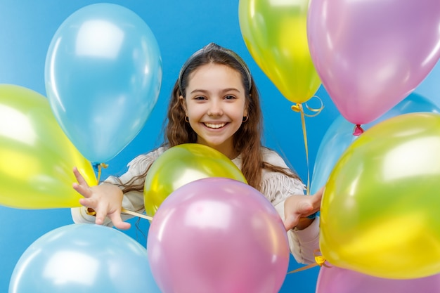Schattige kleine emotionele meisje in witte kleding met gekleurde ballons op blauw