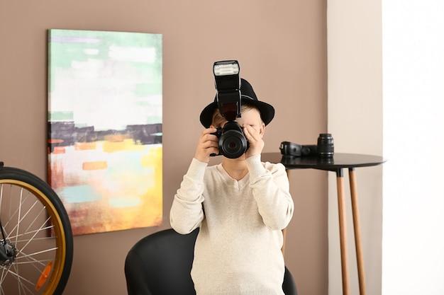 Schattige kleine fotograaf met professionele camera thuis