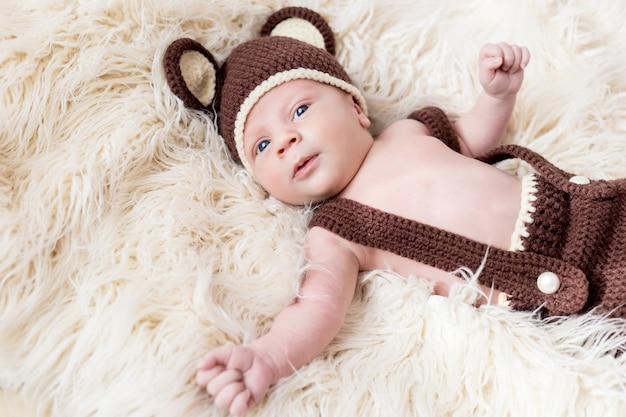 Schattige kleine gelukkige baby ligt in een beerkostuum op een wit. pasgeboren in een hoed met oren op een wit