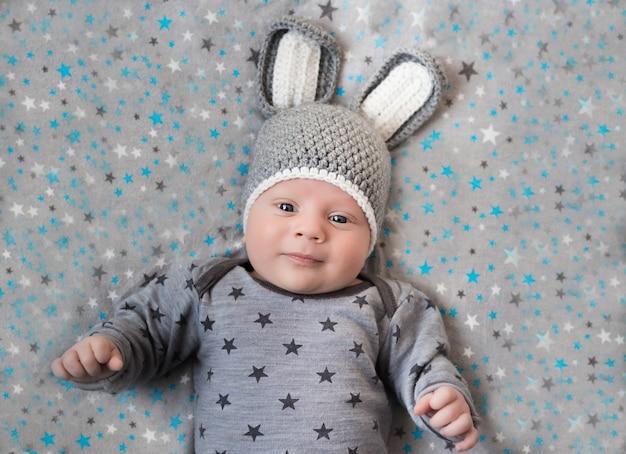 Schattige kleine gelukkige baby ligt in een haas kostuum op een wit. pasgeboren in een hoed met oren op een wit