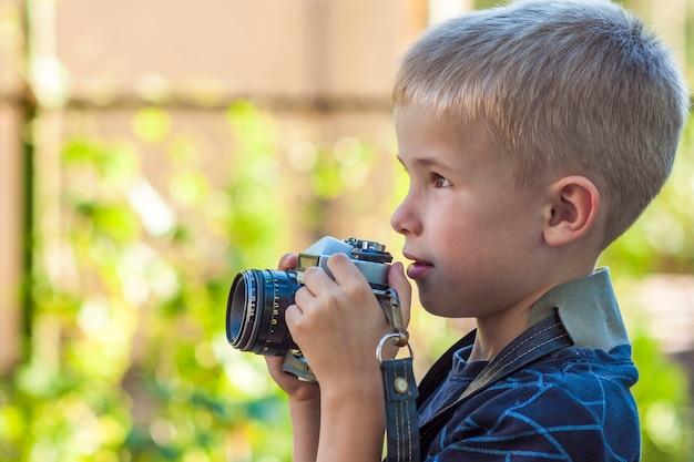 Schattige kleine gelukkige jongen met vintage fotocamera buitenshuis
