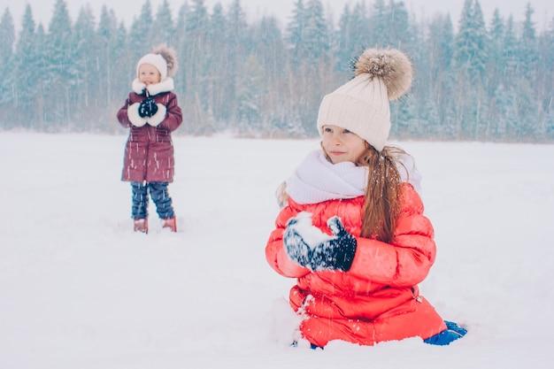 Schattige kleine gelukkige meisjes die in de winter sneeuwdag rodelen.