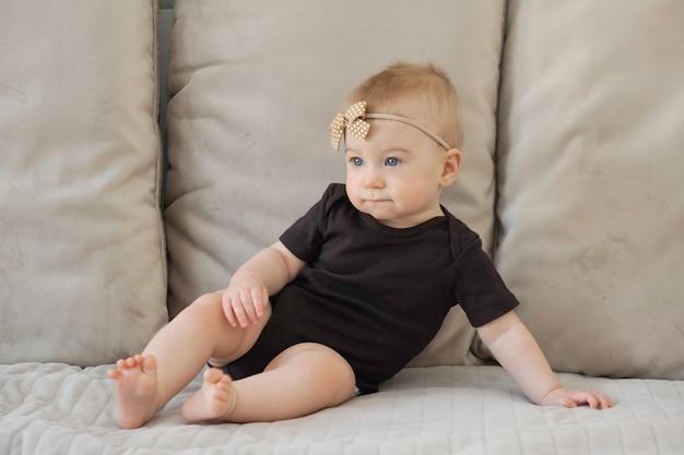 Schattige kleine grappige ernstige kaukasische blonde babymeisje, blauwe ogen, zittend op het oppervlak van beige zachte bankkussens in zwart lichaam met bruine strik, lint
