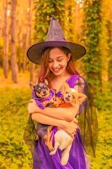 Schattige kleine heks met honden. mooi jong kindmeisje in heksenkostuum buitenshuis. halloween.