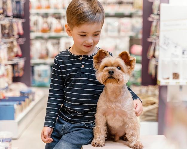 Schattige kleine hond bij de dierenwinkel met eigenaar