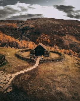 Schattige kleine hut met stenen pad bovenop een heuvel