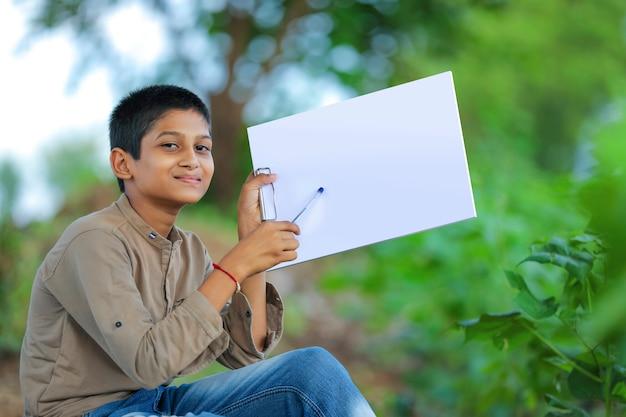 Schattige kleine indiase / aziatische jongen met blocnote met pen