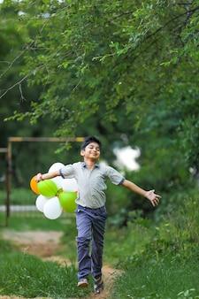 Schattige kleine indiase jongen met driekleurige ballonnen en het vieren van onafhankelijkheid of dag van de republiek india
