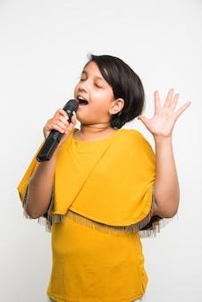 Schattige kleine indiase meisje zingen in microfoon, geïsoleerd op witte achtergrond