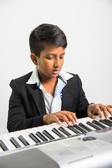 Schattige kleine indiase of aziatische jongen die piano of keyboard speelt, een muziekinstrument, op witte achtergrond