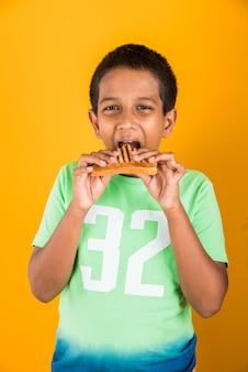 Schattige kleine indiase of aziatische jongen die smakelijke hamburger, sandwich of pizza eet in een bord of doos. staande geïsoleerd over blauwe of gele achtergrond.