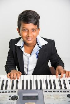 Schattige kleine indiase of aziatische jongen spelen piano of keyboard, een muziekinstrument, op witte achtergrond