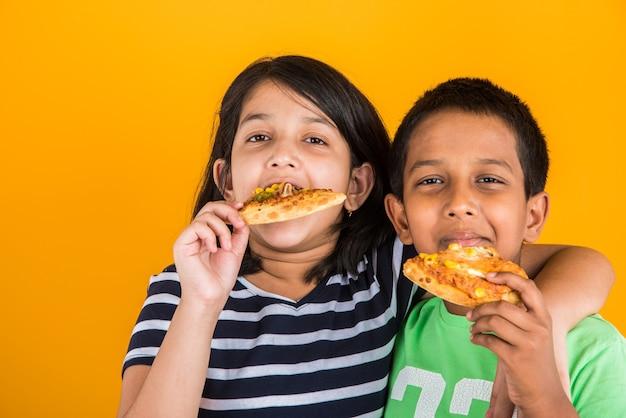 Schattige kleine indiase of aziatische kinderen die smakelijke hamburger, sandwich of pizza eten in een bord of doos. staande geïsoleerd over blauwe of gele achtergrond.