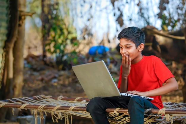 Schattige kleine indische / aziatische jongen die of spel met laptop computer bestudeert speelt