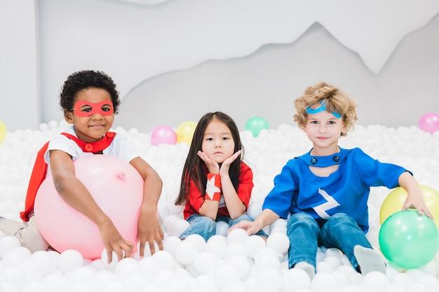 Schattige kleine interculturele vrienden in kostuums spelen met witte ballonnen in de kinderkamer of kleuterschool