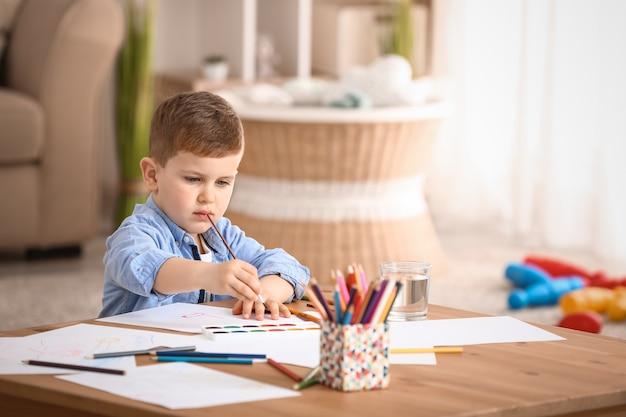 Schattige kleine jongen aan het schilderen thuis