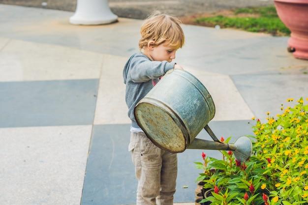 Schattige kleine jongen bloemen gieter water geven