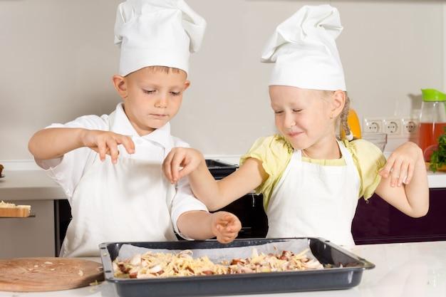 Schattige kleine jongen chef-koks ingrediënten op pizza zetten op witte tafel.