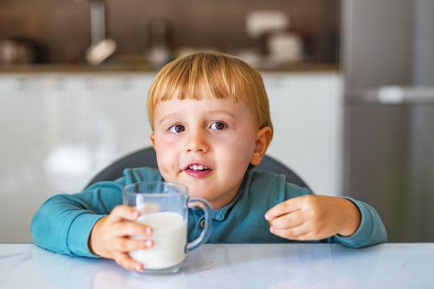 Schattige kleine jongen consumptiemelk of yoghurt en karamel eten tijdens het ontbijt in de keuken in de ochtend