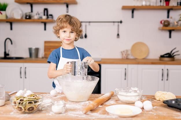 Schattige kleine jongen die bloem over de kom zift terwijl hij deeg gaat maken voor zelfgemaakt gebak in de keuken