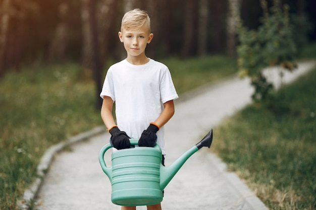 Schattige kleine jongen die een boom plant op een park