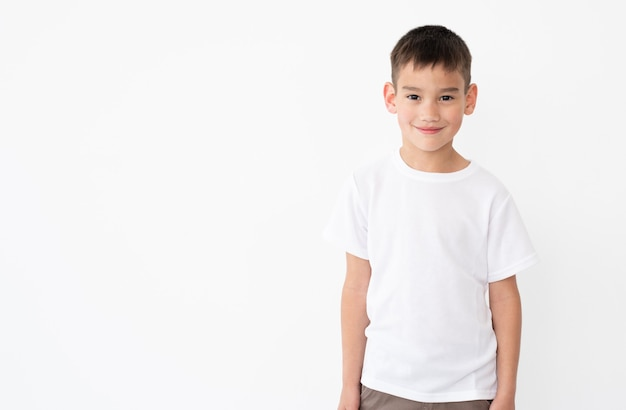 Schattige kleine jongen die een leeg wit t-shirt draagt