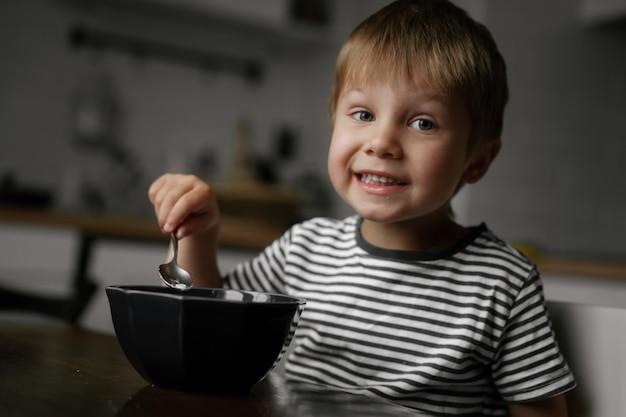 Schattige kleine jongen die havermout eet als ontbijt be
