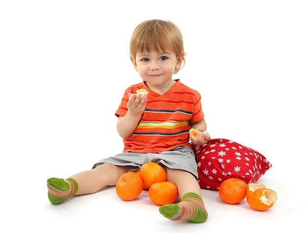 Schattige kleine jongen die mandarijnen eet, geïsoleerd op wit