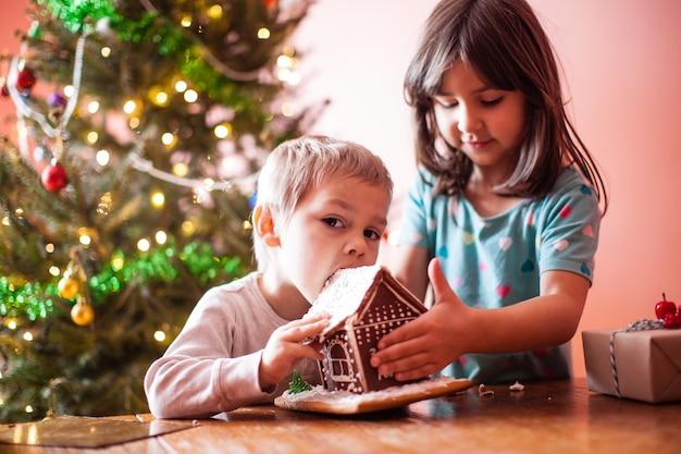 Schattige kleine jongen die met kerst aan een peperkoekkoekjeshuis knabbelt